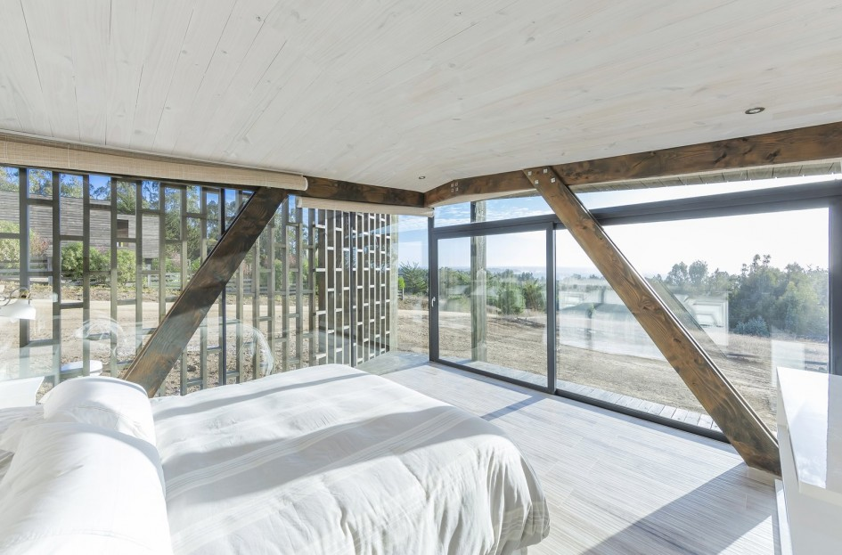 This beach house wrapped in a pavilion of slatted pine wood is located on a privileged western slope of the coastal mountain range in Punta de Lobos, Chile and presents amazing views of the South Pacific. Designed by LAND Arquitectos, the idea of the house is to optimize the views of the sea, maximize northern sunlight and offer protection from the south wind.